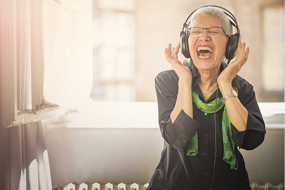 Elderly woman listening to music on her over-ear headphones.
