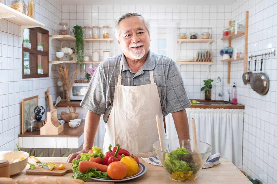 Elderly man in kitchen getting ready to cook with vegetables to counteract vitamin B12 deficiency.