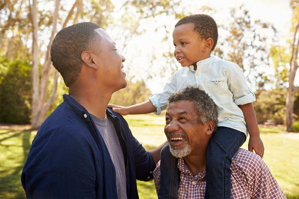 Three generations of men laughing together in a park, otherwise known as the sandwich generation.