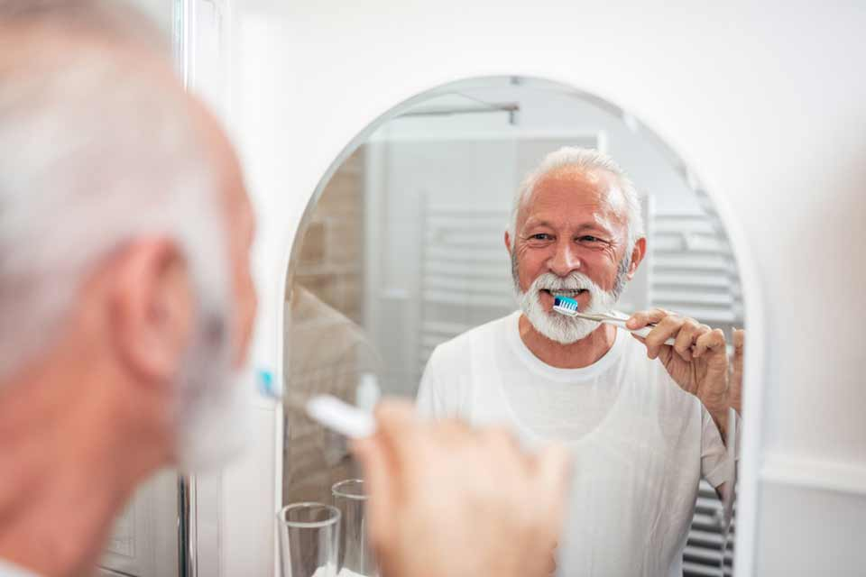 Elderly man brushing his teeth in front of the mirror.
