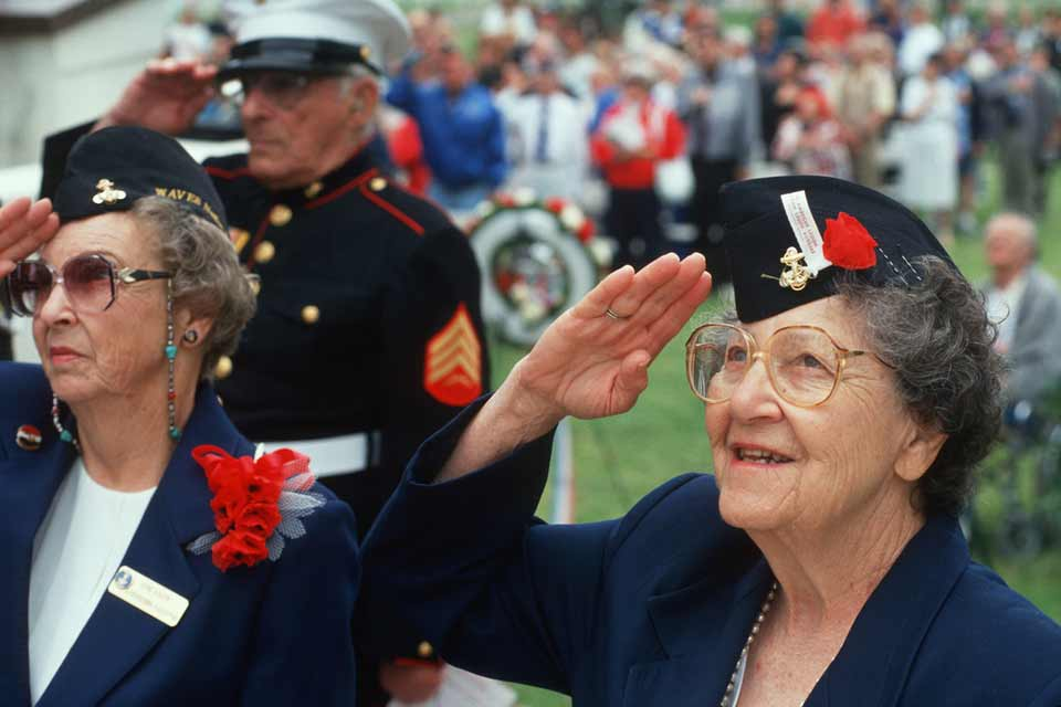 Two female veterans and a male veteran marine saluting a ranking officer at a group event.
