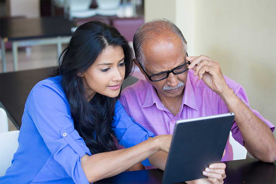 Father and daughter monitoring an elderly loved one on a tablet.