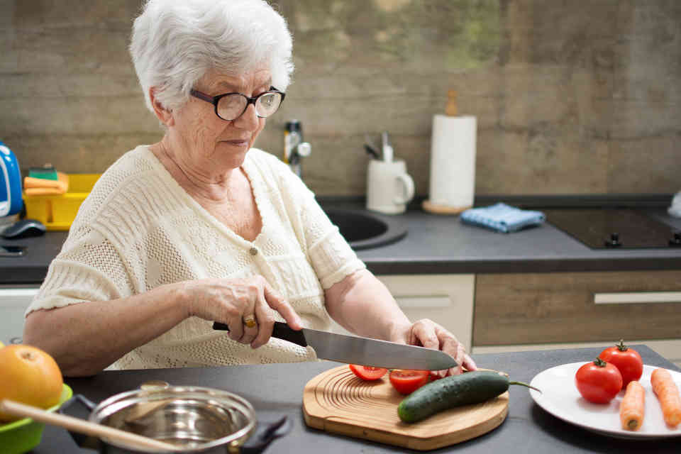 Elderly woman cutting vegetables as part of her activities of daily living (ADLs)
