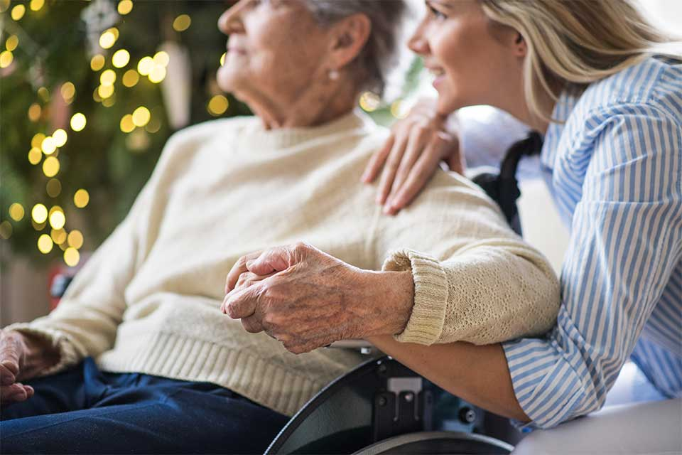 Elderly female in wheelchair holding hands with caregiver.