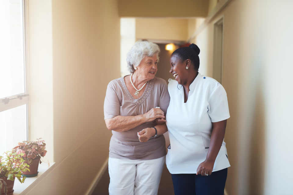 Caregiver helping an elderly woman walk down the hallway of their building.