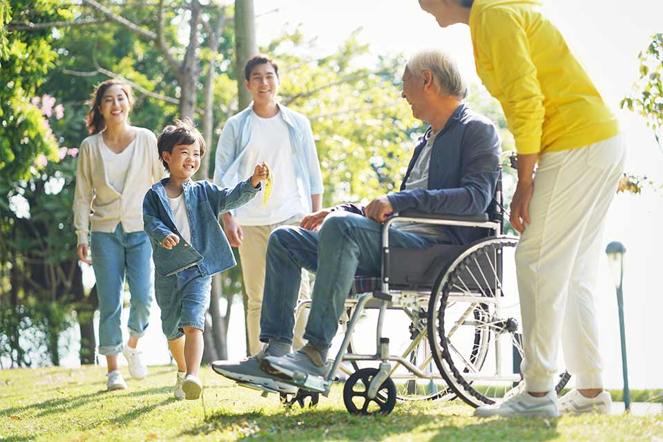 Elderly man in a wheelchair and his family gather in a park to enjoy the day