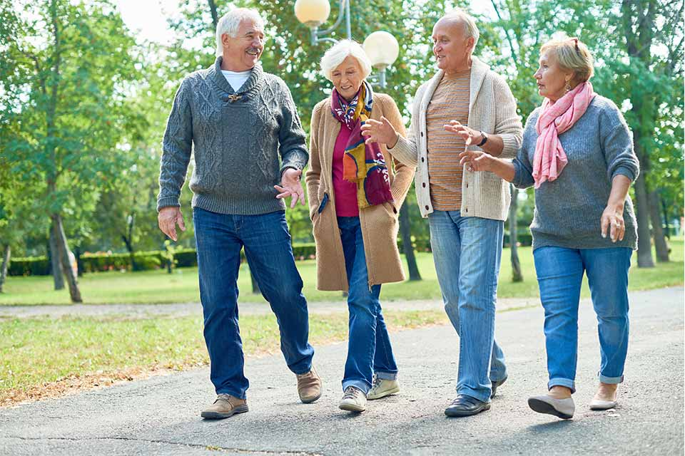 Two elderly couples walking in the park outside their independent living community