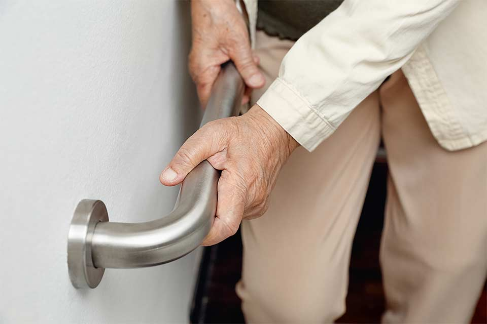 Elderly woman using a handrail to prevent an unexpected fall.