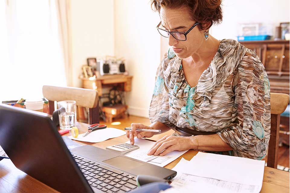 Female working on finances to find ways to pay for memory care.
