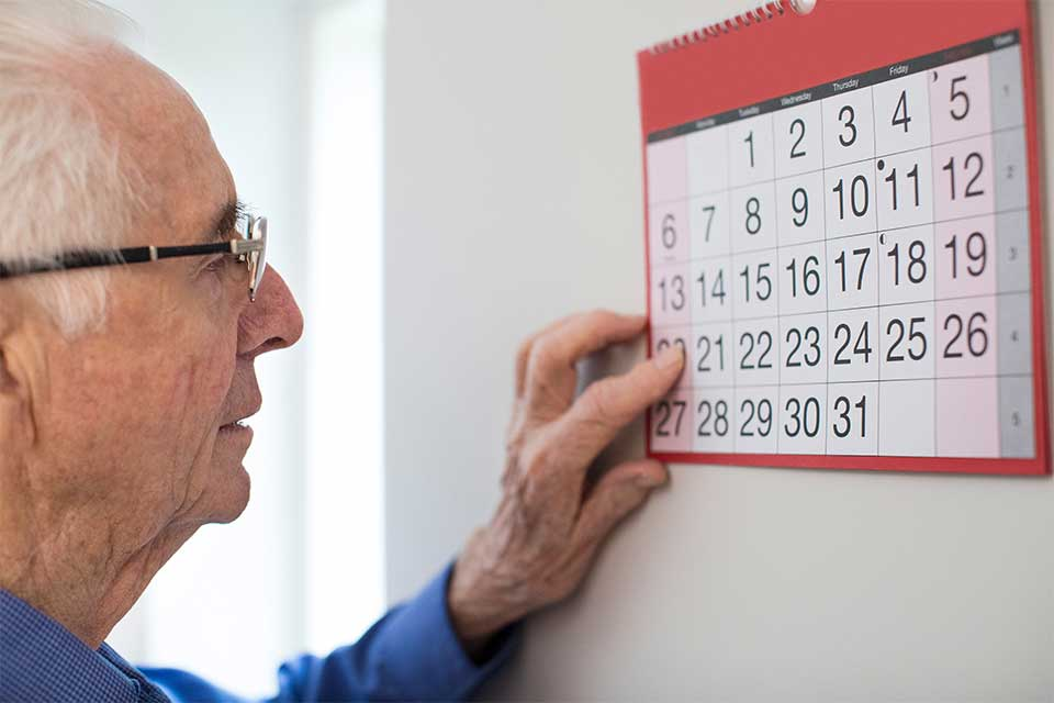 Elderly man counting days on a hanging wall calendar.