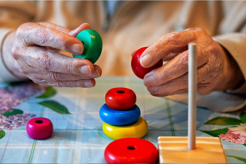 Elderly person using tactile games to stimulate and preserve memory.