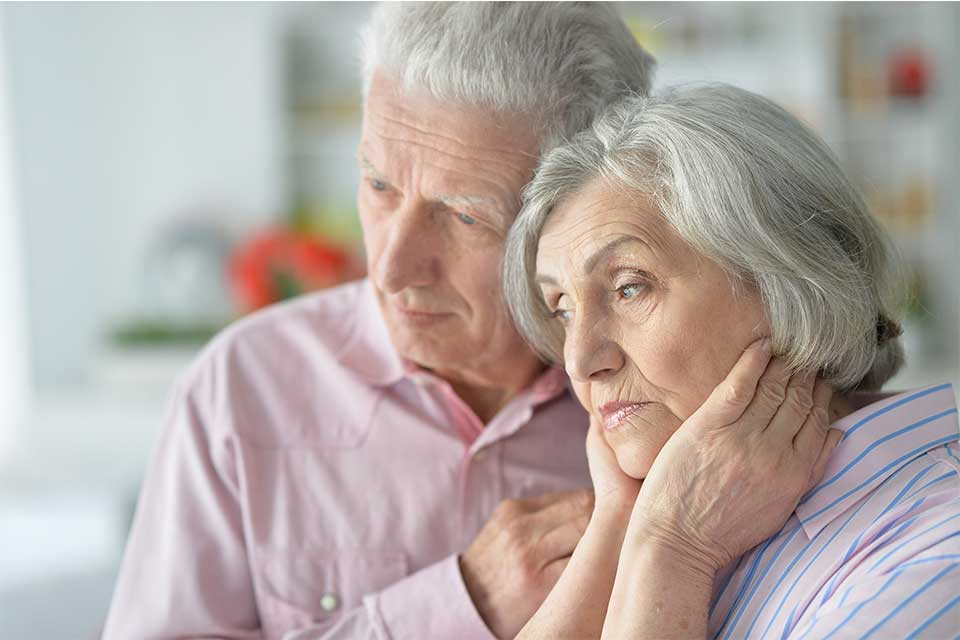 Elderly couple comforting each other after learning of a dementia diagnosis.