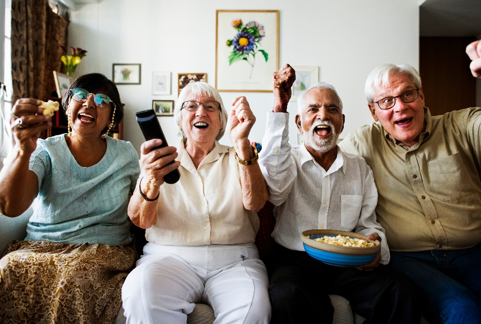 A group of seniors gathers in the living room to watch sports and have fun.