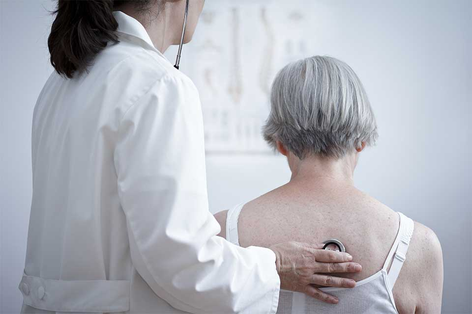 Elderly woman having her lungs checked by a female doctor.