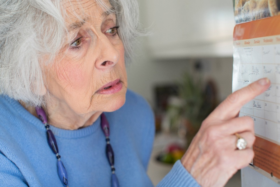 Confused elderly woman looking at a calendar.