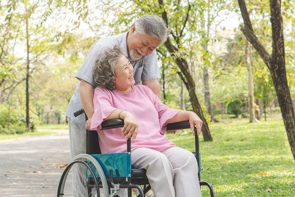 Male caregiver taking his female patient for a walk in her wheelchair in the park.