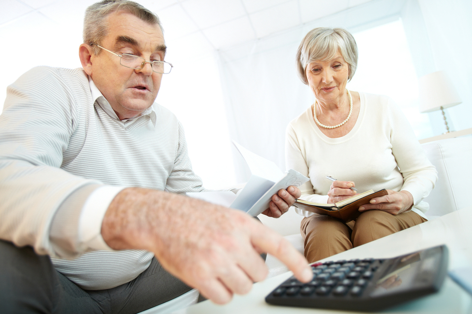 Senior couple calculates the costs of independent senior living.