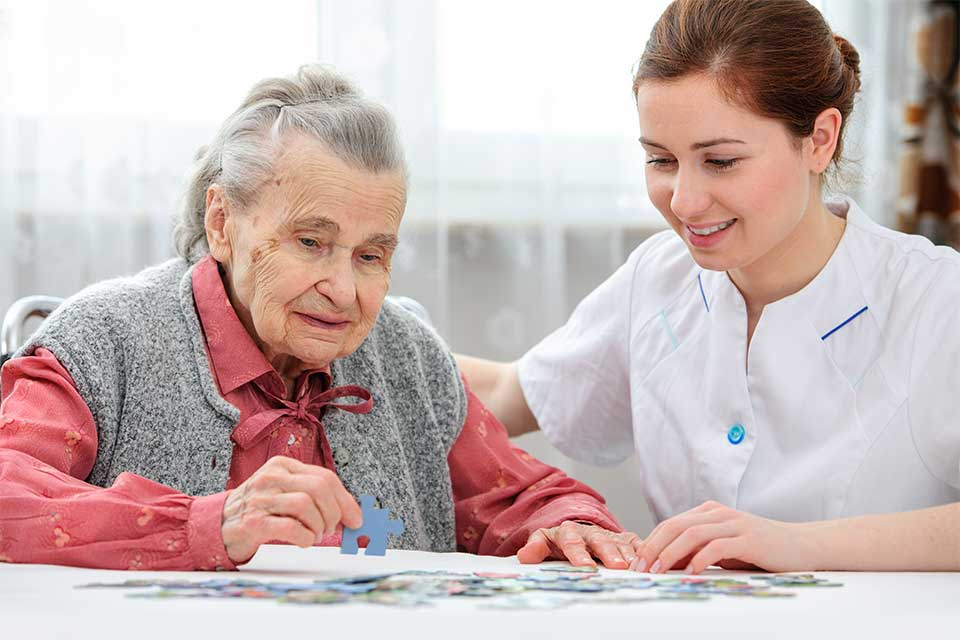 Elderly woman in dementia care putting together a puzzle.