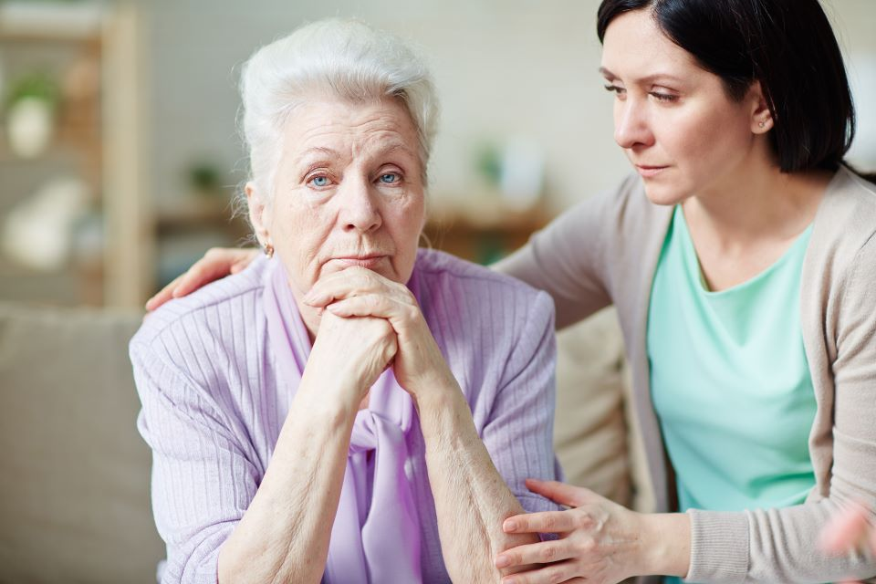 Daughter sits with upset elderly mother.