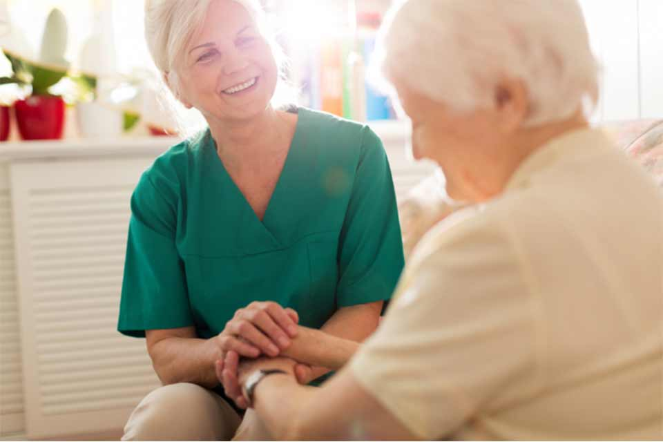 Memory care caregiver holding the hands of a patient and smiling.