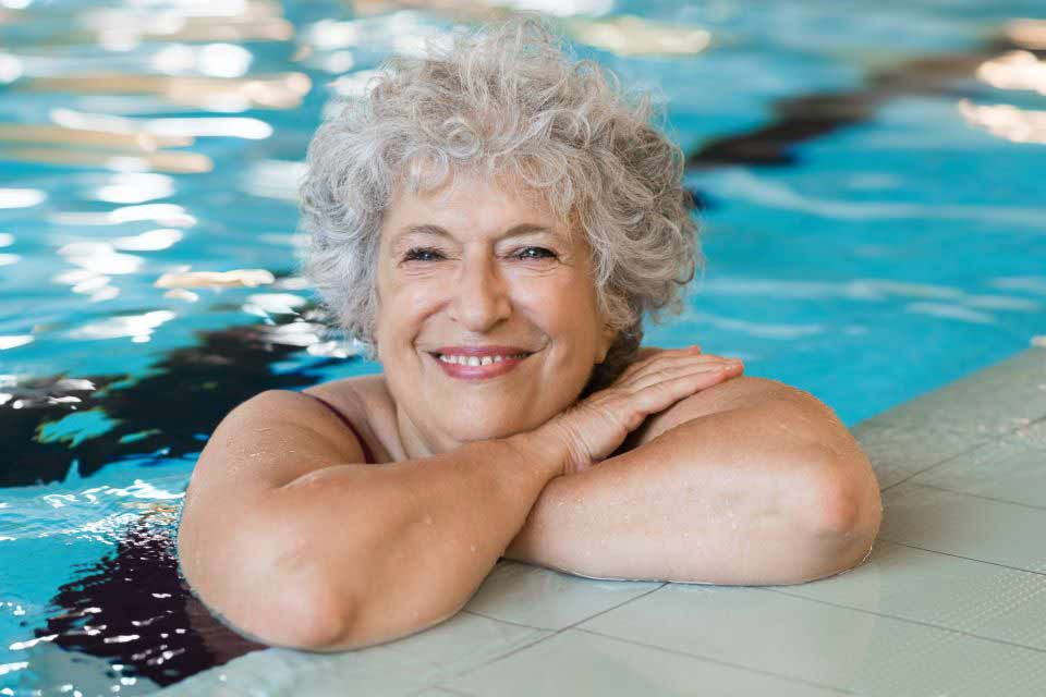 Elderly woman resting on the edge of a swimming pool.