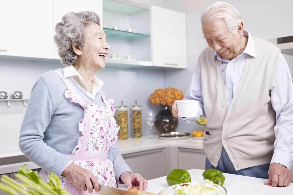 Elderly couple laughing and cutting vegetables for dinner.