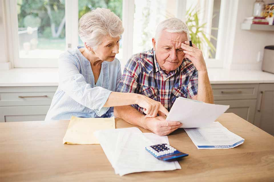 Elderly couple sitting at the kitchen island struggling to understand the various costs of nursing homes.