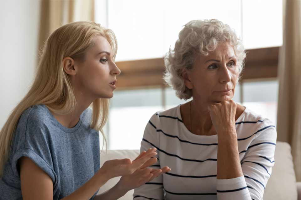 Young woman trying to have a conversation with her aging mother.