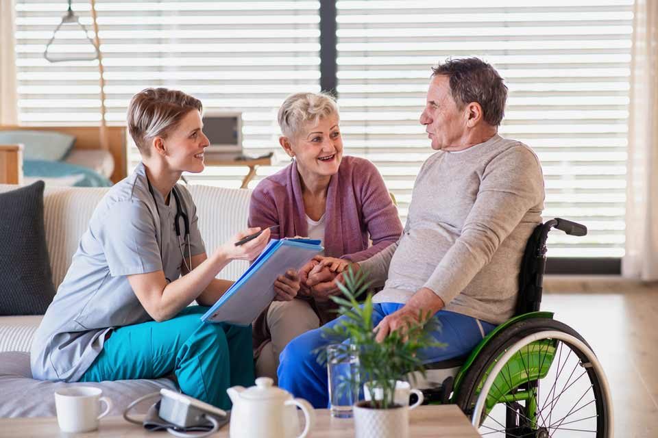Elderly man in a wheelchair and elderly woman talking to their nurse in a nursing home.